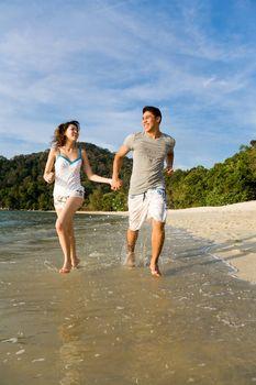 happy couple running along the beach