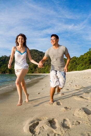 loving young couple enjoying themselves running along the beach happily