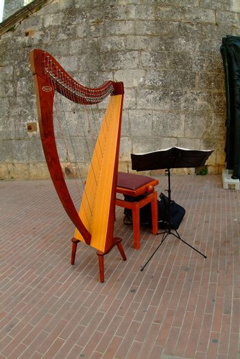 red harp with seat and music stand