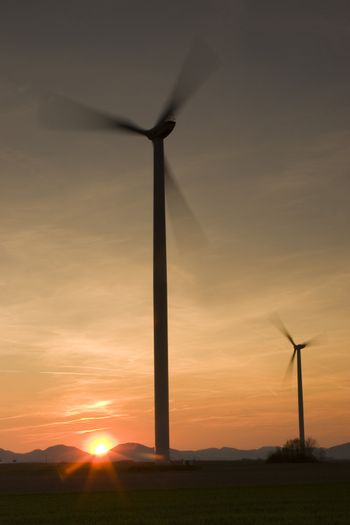 Two motion blurred wind-turbines at sunset or sunrise