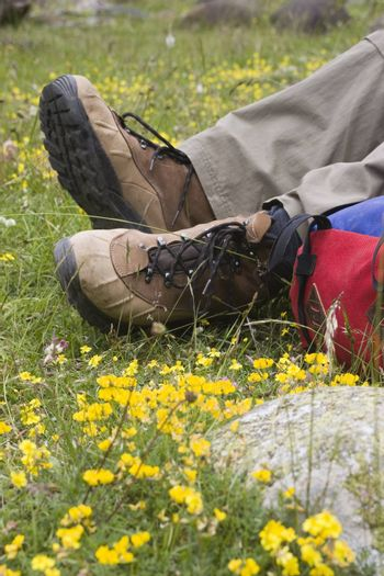 Boots of a mountaineer and rucksack on a meadow - focus on the boots.