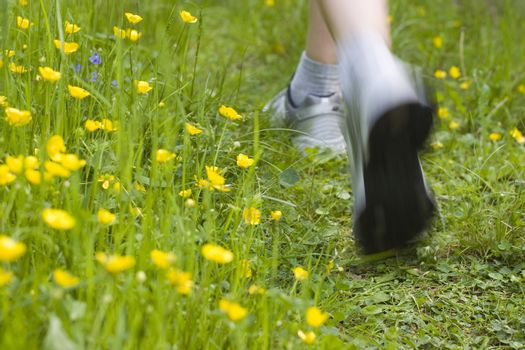 Close-up of female legs while running through a meadow with yellow flowers