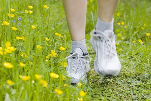 Female legs running in on a path with flowers and grass