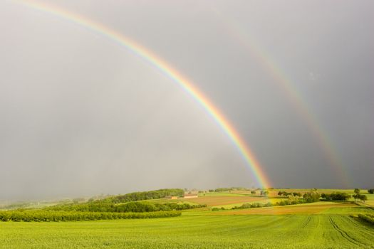 Half rainbow over a rural landscape with intensive colors