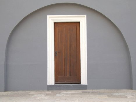 Brown wooden door in a grey archway