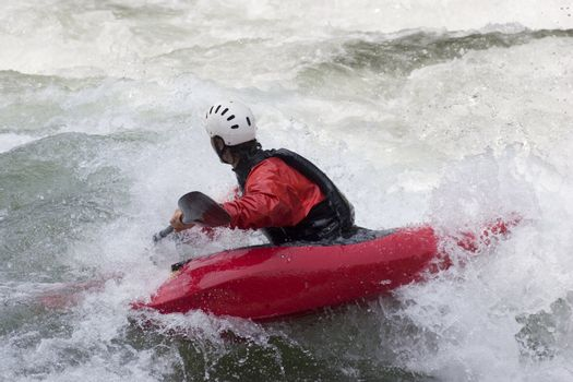 Red kayak in the rapids of a whitewater river. Noguera Pallaresa - Spain.