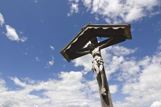 Wooden cross in against cloudscape