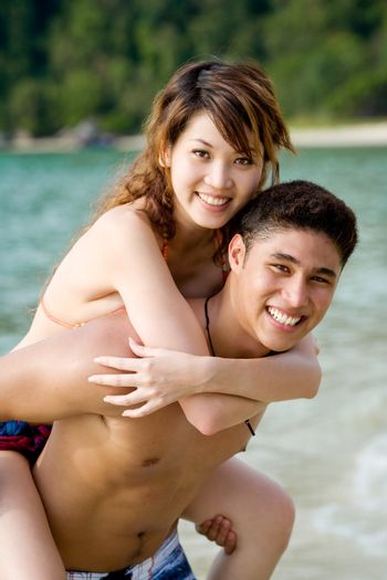 couple carrying piggyback on a tropical beach