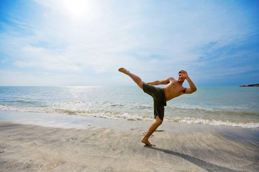 a energetic guy kick boxing by the beach in beautiful sky