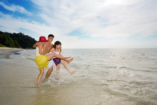 3 friends playing with sea water at the beach