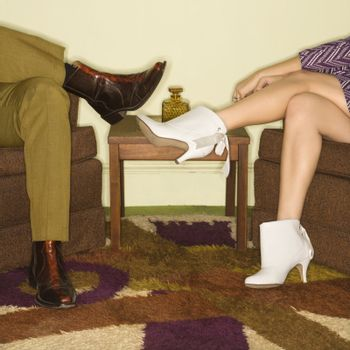 Close-up of seated Caucasian mid-adult male and female legs wearing vintage boots.