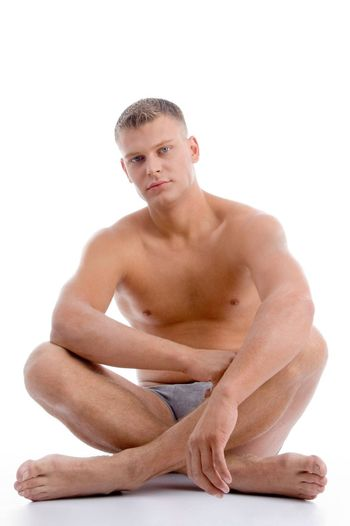 sitting muscular man on an isolated white background