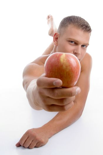 laying fit guy showing apple on an isolated background