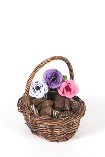 dark brown basket filled with chocolate and roses