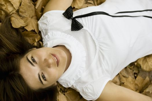 Young beautiful woman lying in the autumn park