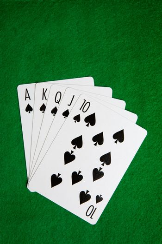 A royal flush in spades on a green felt background