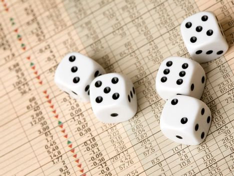 Dice and stock market charts in the newspaper