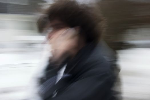 A motion blur abstract of a person walking in a hurry talking on a cell phone