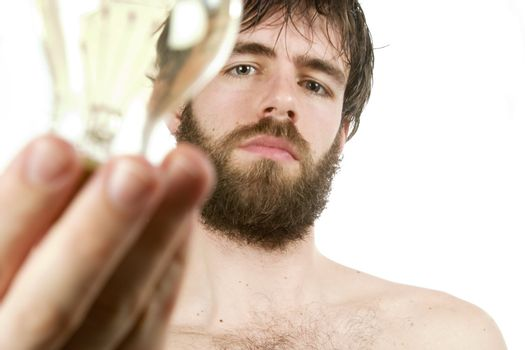 A concept image displaying a young bearded male, holding a light bulb. Fresh New Idea.