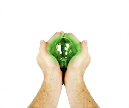 A green energy concept image.  A pair of mens hands holding a lightbulb that is glowing green.