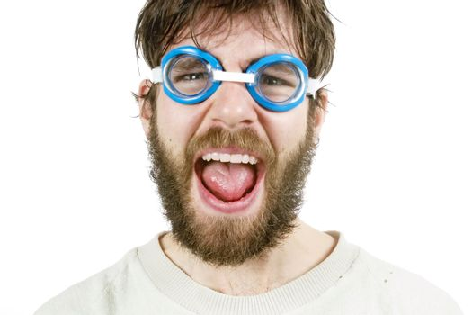 A funny looking young male with a beard and swimming goggles looking discusted or angry.