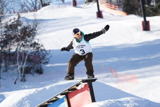 A snowboarder rides on a rail in a competition