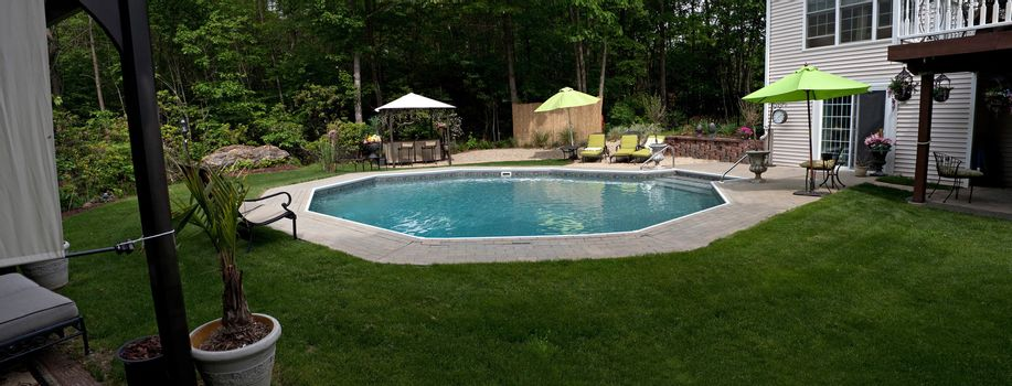 A wide angle panoramic view of a luxurious in ground pool and patio.  This partly wooded backyard offers the same level of luxury found in many vacation resorts.