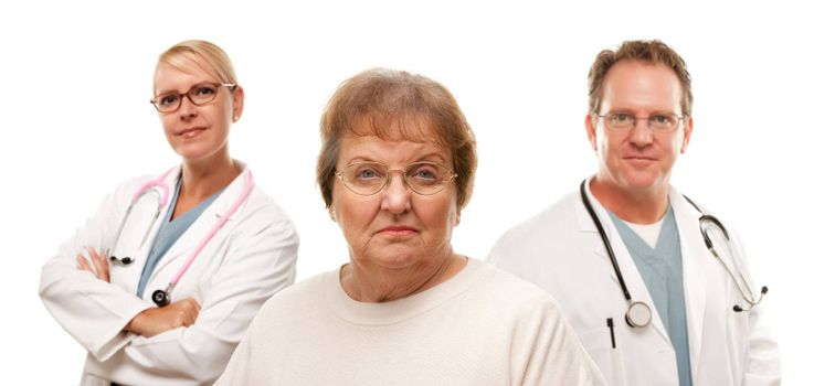 Concerned Senior Woman with Doctors Behind Isolated on a White Background.
