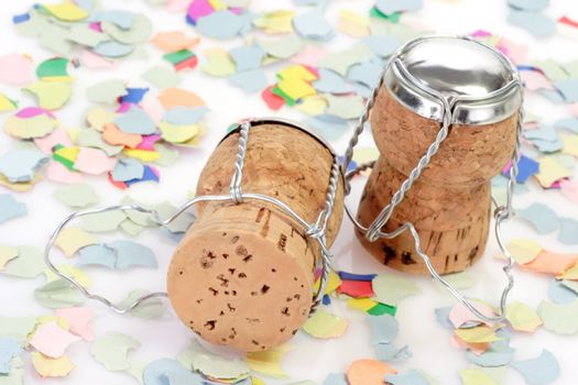 Two champagne corks and confetti on white background