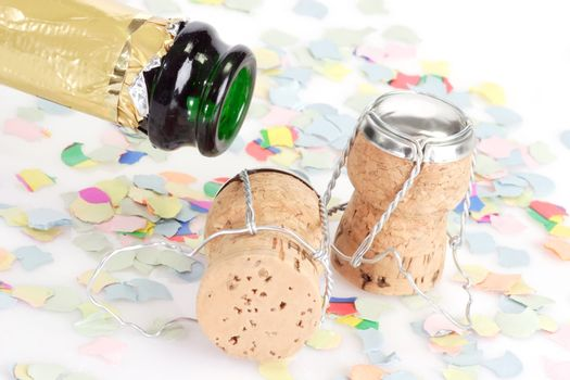Empty champagne bottle, two corks and confetti on white background