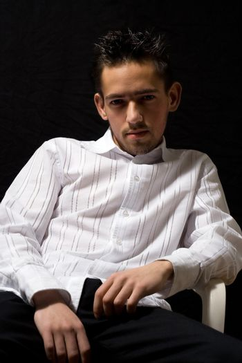 man in white shirt sitting in a chair