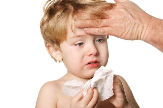 A sick child blows his nose while his father touches his forehead