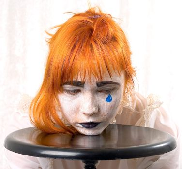Clown makeup girl with red hair and blue tear