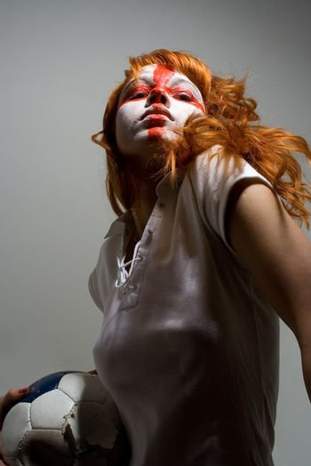 English football makeup girl holding worn soccer ball, looking directly into camera