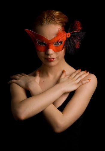 mysterious lady in red mask holding her arms in w shape
