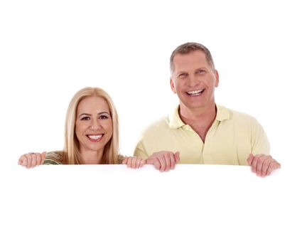Middle aged couple standing behind a blank white board and smiling over a isolated white background
