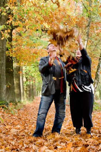 Older couple tossing leafs