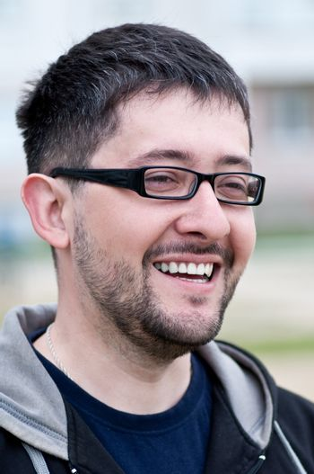 Portrait of a young smiling bearded man wearing glasses