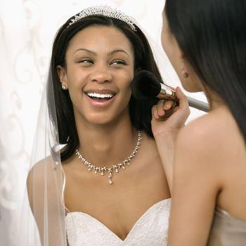 Asian bridesmaid applying makeup to African-American bride.