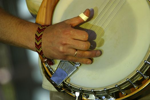 Part of a banjo and hand man close-up