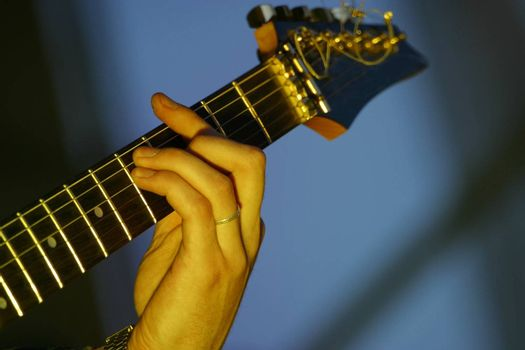 Part of a guitar and hand man close-up