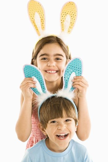 Portrait of boy and girl wearing rabbit ears smiling.