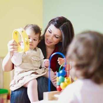 two little girls and female teacher in kindergarten