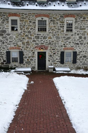 stone building decorated for Christmas with wreath on door