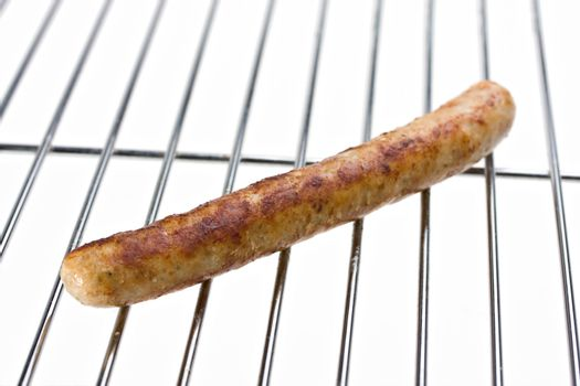 grilled sausage on a grill isolated on white