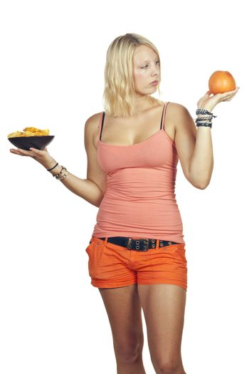 Attractive girl deciding to eat junk food or fruit
