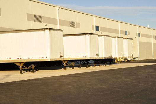 many trucks lined up at an industrial warehouse