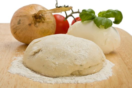 yeast dough, cheese, tomatoes and an onion on a wooden board
