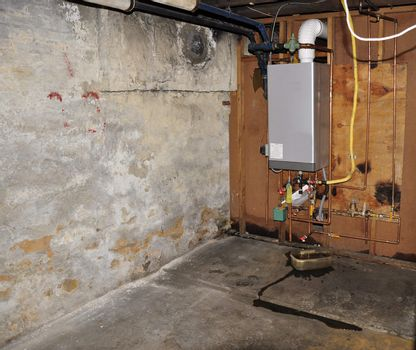 furnace heating unit on wall in an old basement