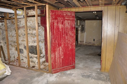 an old red wooden door in an old basement